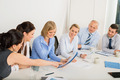 Business Team Sitting Around Meeting Table - PhotoDune Item for Sale