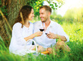 Picnic. Young Couple relaxing and drinking Wine in a Park - PhotoDune Item for Sale