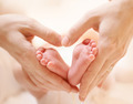 Tiny Newborn Baby's feet on female Heart Shaped hands closeup - PhotoDune Item for Sale