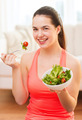 smiling teenage girl with green salad at home - PhotoDune Item for Sale