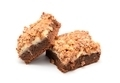 Brownies cake with cottage cheese powdered by pieces of chocolate nut bar on a white background. - PhotoDune Item for Sale