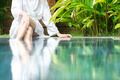 Woman resting at pool with feet in water. - PhotoDune Item for Sale