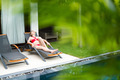 Woman relaxing on chaise longue near pool. - PhotoDune Item for Sale