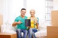 couple relaxing on sofa with tablet pc in new home - PhotoDune Item for Sale
