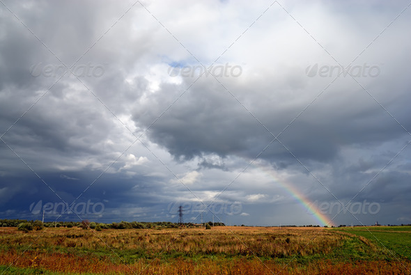 Clouds and rainbow above meadow - Stock Photo - Images