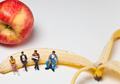 Miniature people in action sitting on a banan - PhotoDune Item for Sale