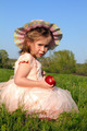 little girl eating apple on meadow - PhotoDune Item for Sale