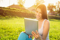Happy young woman with tablet in park on sunny summer day - PhotoDune Item for Sale