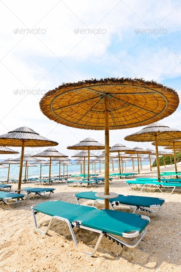 Beach umbrellas and chairs on sandy seashore - Stock Photo - Images