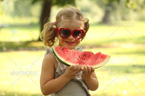 little girl with sunglasses eat watermelon - Stock Photo - Images