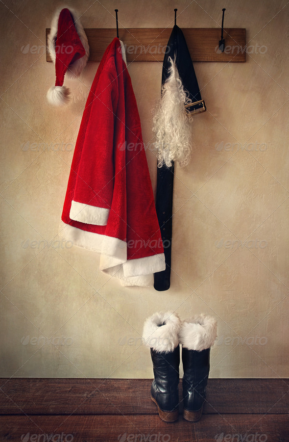 Santa costume with boots on coat hook - Stock Photo - Images