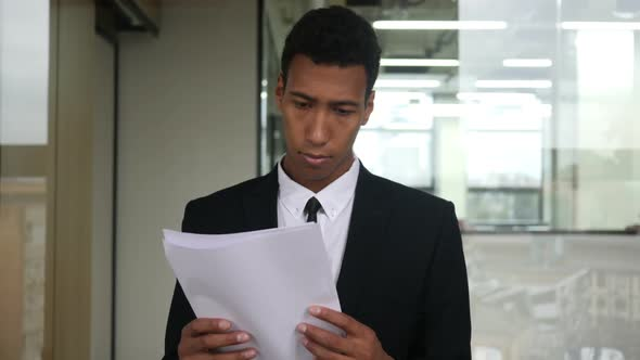 Download Black Businessman Reading Documents in Office nulled download