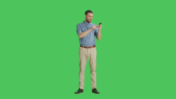 VideoHive Man Holding Smartphone Smartphone and Background are Green Screen 19467239