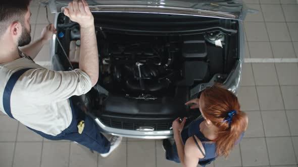VideoHive Man and Woman Repairing Car 19662497