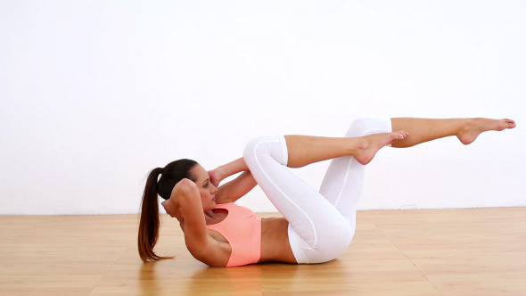Fit Model Doing Abdominal Crunches And Kicking Leg