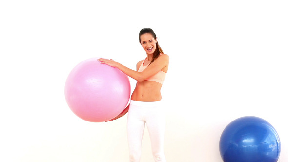 Fit Model Holding Exercise Ball And Smiling