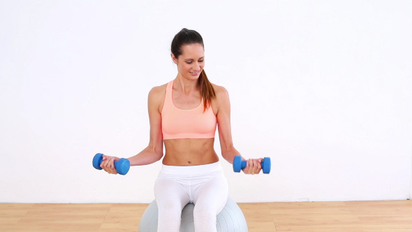 Fit Model Sitting On Exercise Ball Lifting