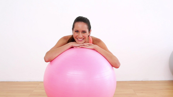 Fit Model Leaning On Pink Exercise Ball Smiling