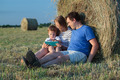 Family of three with pad in the field with hay rolls - PhotoDune Item for Sale