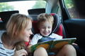 Boy holding book sitting in a car with mother - PhotoDune Item for Sale
