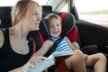Mother reading a book to son in the car - PhotoDune Item for Sale