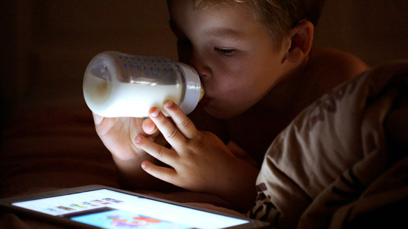 Boy Drinking Milk Looking At Touchpad