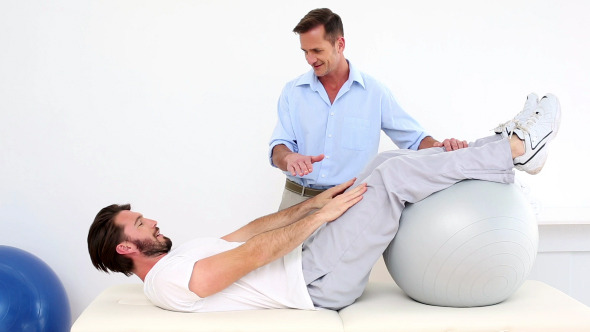 Physical Therapist Helping His Patient Do A Sit Up