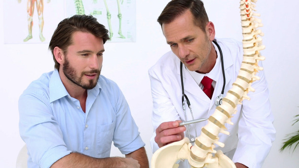 Patient Listening To Doctor Explain Spine Model