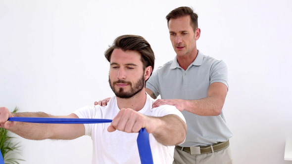 VideoHive Physiotherapist Checking Patient Pulling A Band 8487754