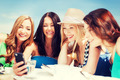 girls looking at smartphone in cafe on the beach - PhotoDune Item for Sale