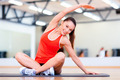 smiling woman stretching on mat in the gym - PhotoDune Item for Sale