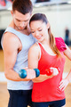 two smiling people working out with dumbbells - PhotoDune Item for Sale