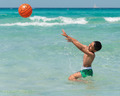 child playing with ball in the turquoise sea - PhotoDune Item for Sale
