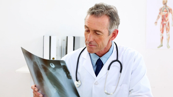 Mature Doctor Looking At Xray At His Desk