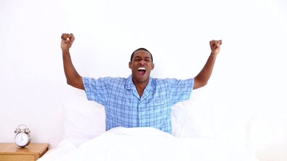 Happy Man Yawning And Stretching Sitting In Bed 2