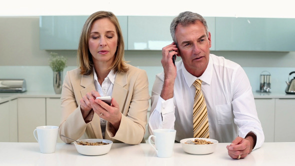 Couple Having Breakfast And Using Phones