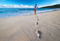 Woman at beautiful beach. Focus on footprints. - PhotoDune Item for Sale