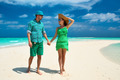 Couple in green on a beach at Maldives - PhotoDune Item for Sale
