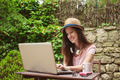 Young woman with straw hat working with laptop in outdoors. - PhotoDune Item for Sale