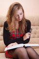 Young woman reading thick book on a sofa - PhotoDune Item for Sale