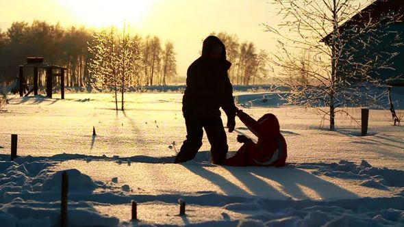 Young Couple Hugging And Falling In The Snow