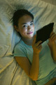 Young asian woman lying on bed and using digital tablet in the night. - PhotoDune Item for Sale