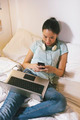 Casual young woman sitting on bed and using smart phone at home. - PhotoDune Item for Sale