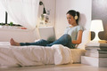 Casual young woman sitting on bed and using laptop at home. - PhotoDune Item for Sale