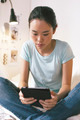 Casual young woman sitting on bed and using digital tablet at home. - PhotoDune Item for Sale