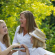 Mother and daughters laughing while eating berries outside - PhotoDune Item for Sale