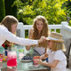 Mother putting hat on younger daughter during breakfast outdoors - PhotoDune Item for Sale