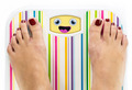 Feet on bathroom scale with laughing cute face on dial - PhotoDune Item for Sale