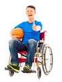 hopeful young man sitting on a wheelchair with a basketball and thumb up in studio - PhotoDune Item for Sale