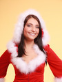 Portrait woman wearing santa claus costume on yellow